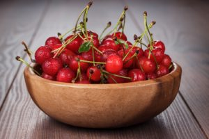 wooden bowl full of cherries on the table