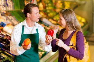 Miembro del personal ayudando al cliente elegir entre pimientos naranjas o rojos.