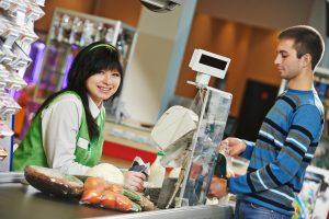 Cliente comprando comida en el supermercado y haciendo el check out con el cajero de la tienda.