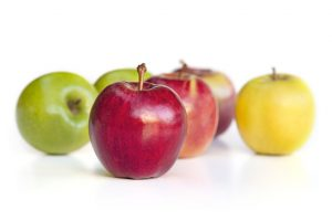Selection of apple varieties, with red delicious apple out in front. Isolated on white.