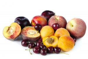 Variety of stone fruits, including apricots, peaches, nectarines, plums and cherries, isolated on white.