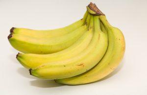 Un montón de plátanos en una mesa blanca todavía con un poco de verde ellos.