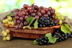 Assortment of ripe sweet grapes in basket, on green background.