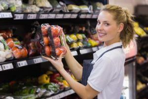 Produce Clerk putting tomatoes on a shelf