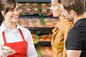 El personal sonríe e interactúa con la pareja en el supermercado.