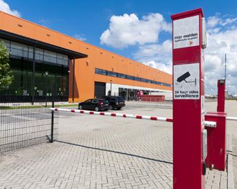 Secured entrance of a modern orange warehouse.