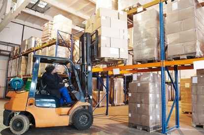 Worker driver of a forklift loader at warehouse loading cardboard boxes on pallet to shelves
