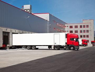 Cargo trucks at an entrance of a warehouse.