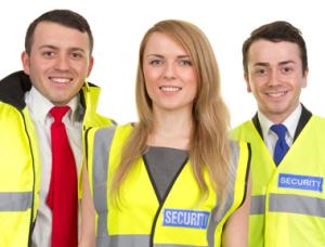Tres miembros del personal de seguridad. Una mujer y dos hombres. Ellos llevan puestos chalecos amarillos brillantes.