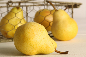 Yellow Pears in and out of a basket on top of a wooden table.