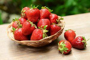 Fresas dulces y maduras en cesta de mimbre en la mesa en el jardín
