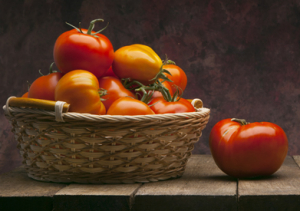 Big red and juicy tomatoes in a basket and one on a wooden table.