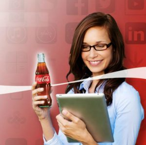 Woman holding Coca Cola bottle and iPad.