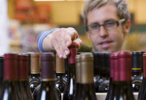 Man grabbing a bottle of wine from shelf.