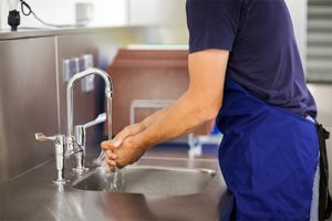Staff member with a blue apron washing his hands.