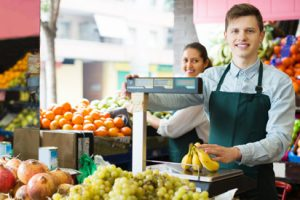 Cashier surrounded by produce and weighing a banana.