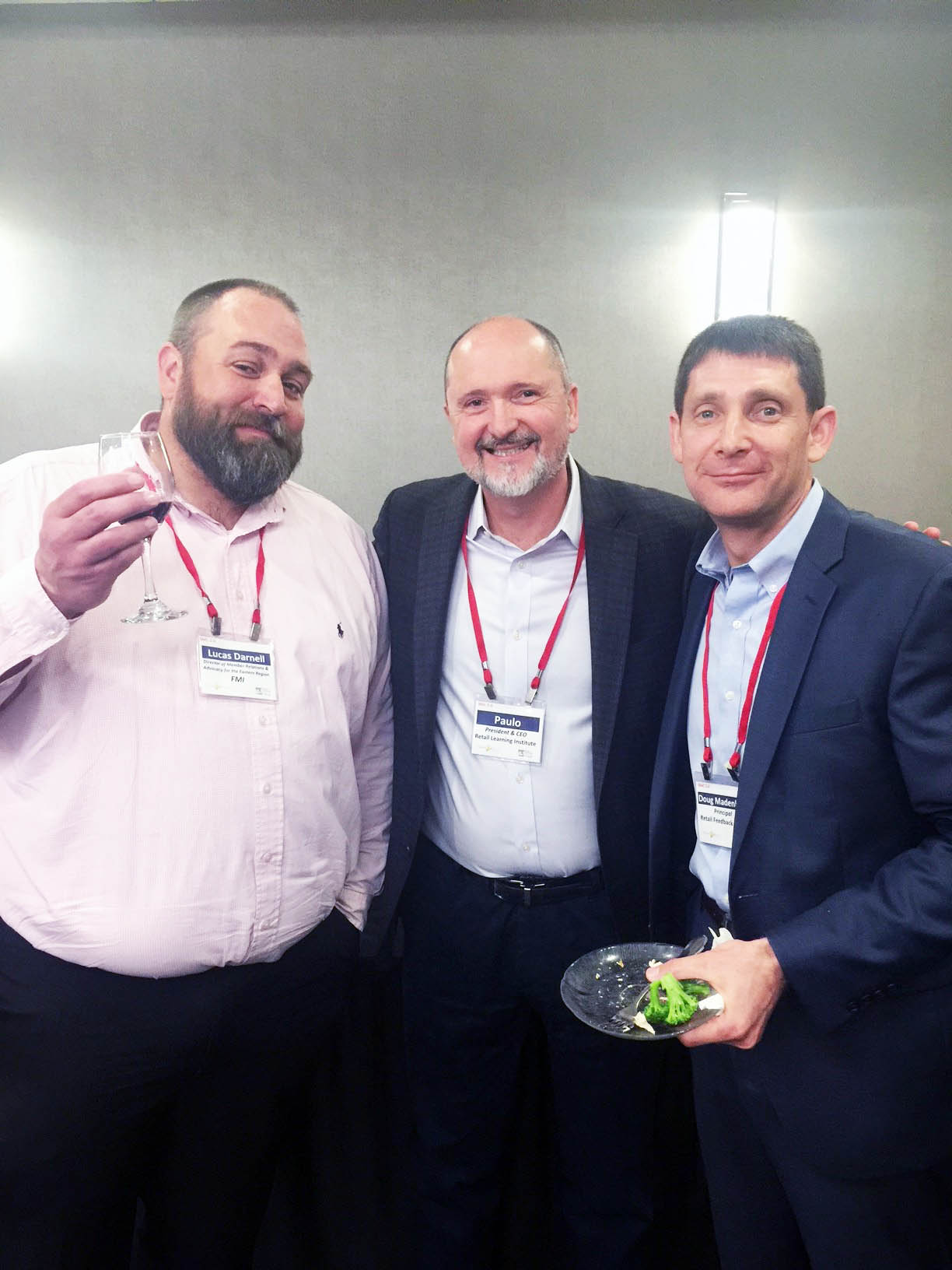 Lucas Darnell, Paulo Goelzer and Doug Madenberg smiling while holding beverages and snacks